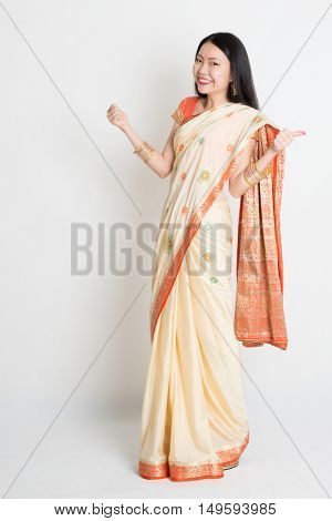 Portrait of young mixed race Indian Chinese woman in traditional sari dress thumbs up, full length on plain background.