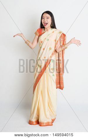 Portrait of surprised young mixed race Indian Chinese female in traditional sari dress, full length on plain background.