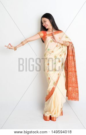 Portrait of young mixed race Indian Chinese woman in traditional sari dress dancing, full length on plain background.