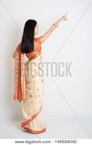 Rear view young mixed race Indian Chinese female in traditional sari dress pointing away, full length on plain background.