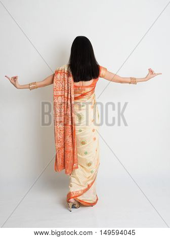 Rear view of young mixed race Indian Chinese woman in traditional sari dress dancing, full length on plain background.