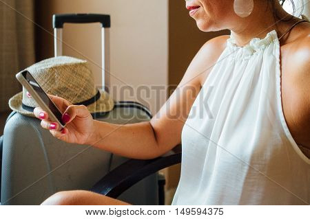 Side view of unrecognizable adult woman in white blouse using smartphone near the suitcase