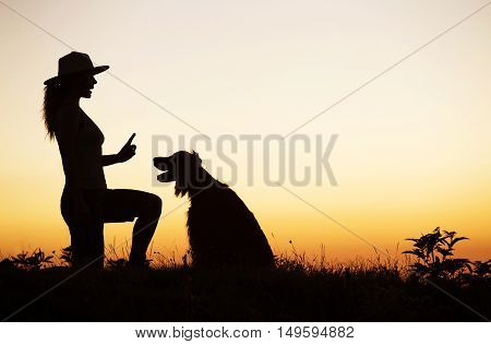 Silhouette of a female as training her happy dog