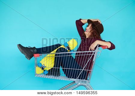Fashion smiling hipster woman having fun wearing a hat with yellow skateboard sitting in the shopping trolley cart over blue background