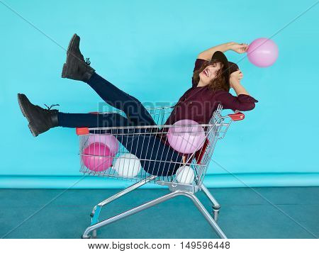 Beautiful brunette girl sitting in shopping cart over a blue turquoise background, color balloons in her one hand