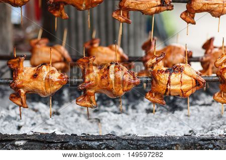 Roast whole chicken on rotating charcoal stove [selected focus at middle frame]