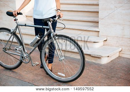 Cropped image of a female biker standing and holding bicycle on the street