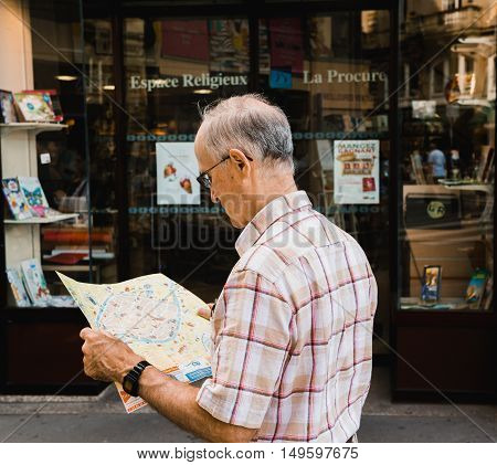 STRASBOURG FRANCE - APRIL 7 2016: Senior man reading map in new city searching for restaurant a sightseeing point or any other point on the map