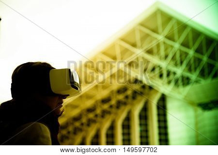 VR virtual reality - Woman wearing a virtual reality headset controlling the experience with hand gesture - looking at green virtual background