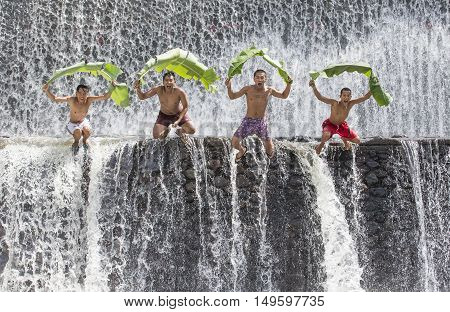 Bali Indonesia September 11th 2016: Young Indonesian boys having fun at a waterfall