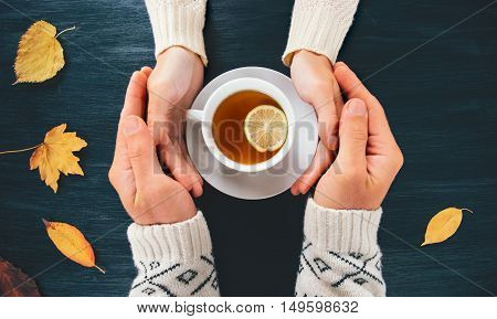 Couple Man and Woman in Love holding hands with hot tea lemon cup on dark wooden table with autumn leaves Romantic relationship feelings concept top view trendy style