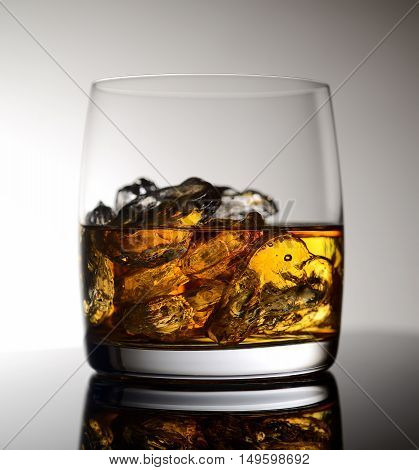 splash in a glass of whiskey and ice on gray background