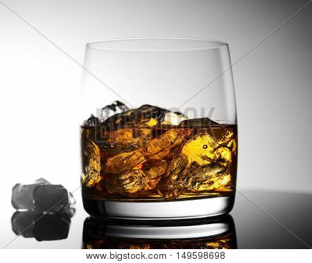 whiskey with ice on blue-white background in transparent glass