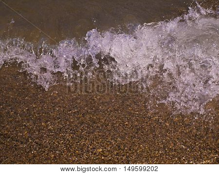 seashore beach wave approaching the shore in the sand