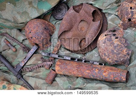 Still life of old military weapons dig up from the ground. Second world war. British automatic gun Sten on the bottom left side.