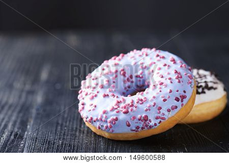 Close view at tasty donuts with blue and vanilla icing on a dark wooden background