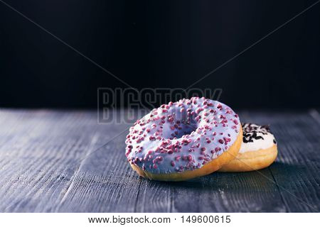 Close view at tasty donuts with blue and vanilla icing on a dark wooden background. With copy space. Toned for art effect