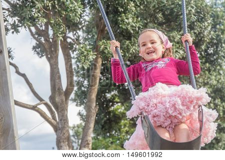 outdoor portrait of young happy child girl swinging on natural background