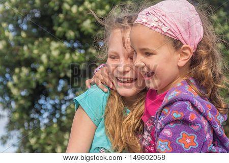 two happy kids - girls - outdoor portrait