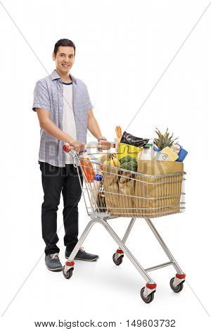 Full length portrait of a man posing with a shopping cart and looking at the camera isolated on white background