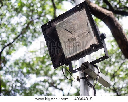Sport light or lamp post with a trees background