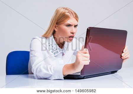 Young businesswoman working at laptop computer. pleasantly surprised dissatisfied girl