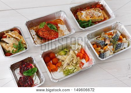 Healthy food delivery, daily ration. Take away of natural organic diet. Fitness nutrition in foil boxes on white wood. Lasagna, vegetables, fish and fruits. Carbs, protein, fat balanced diet
