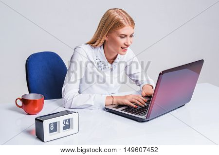 Young businesswoman working at laptop computer. Pretty smiling girl