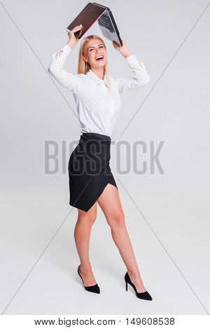 Young businesswoman working at laptop computer. in full growth in office clothes girl. she smiles and contented. fooling around