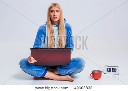 girl in pajamas with a laptop lying on the floor. studying or doing online shopping. work from home. surprise, disgust, asking for help
