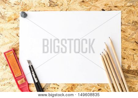 Bunch Of Pencils With Kneaded Eraser, Sandpaper Block And Cutter Knife, On Blank White Sheet Of Pape