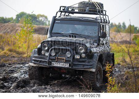 KRASNORECHENSKOYE RUSSIA - SEPTEMBER 24 2016: Russian black brutal off road car UAZ in mud