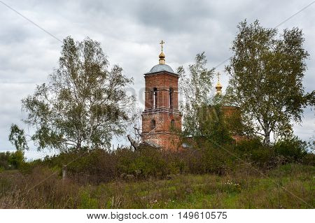 Antique Russian orthodox cathedral building and trees against sky with clouds. Autumn cloudy windy day.
