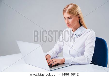 Young businesswoman working at laptop computer. she sits smiling