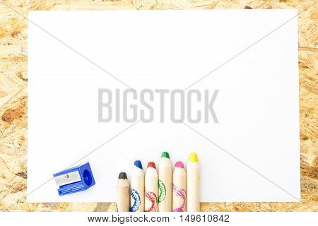 Bunch Of Thick Colorful Pencils For Children And Sharpener, On Blank Sheet Of Paper, On Wooden Surfa