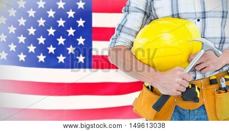 Technician holding hammer and hard hat against rippled us flag