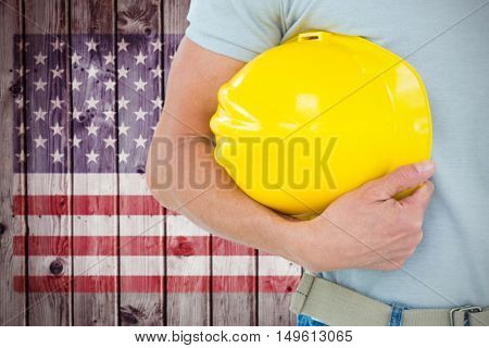 Technician holding hard hat against composite image of usa national flag