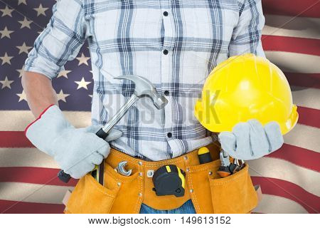 Handyman holding hammer and hard hat against close-up of american flag