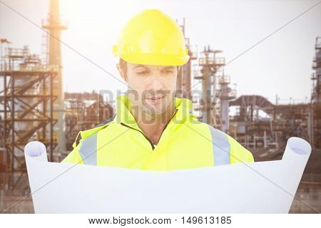 Architect analyzing blueprint against image of factory