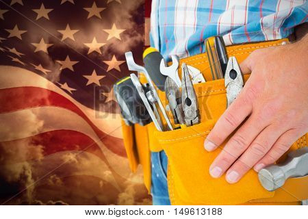 Midsection of handyman wearing tool belt against composite image of digitally generated united states national flag