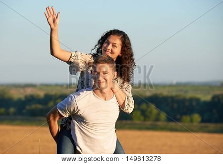 happy young couple walk on country outdoor, romantic people concept, summer season, girl riding on man back and waving