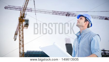 Architect with blueprint against crane and building construction site