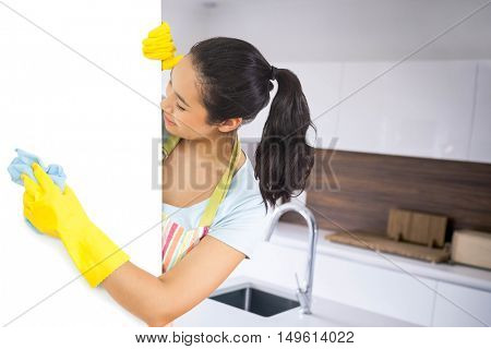 Laughing woman who washes plate form the side against empty modern kitchen