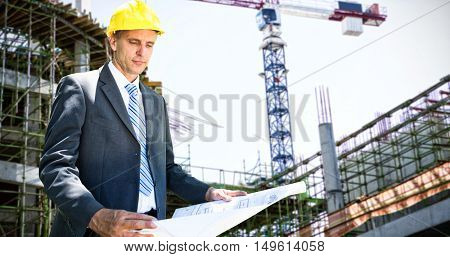 Architect holding blueprint against work in progress in the city