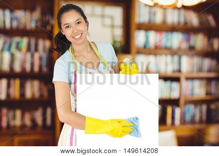 Cheerful woman wiping down white surface against view of studio