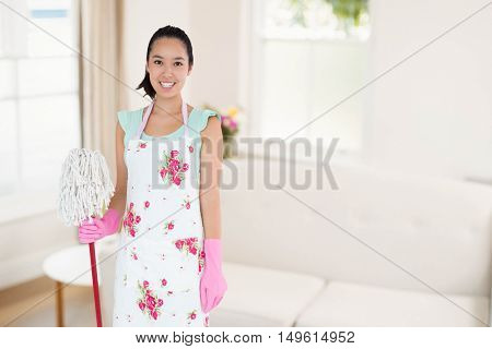 Happy woman with mop and bucket against sitting room