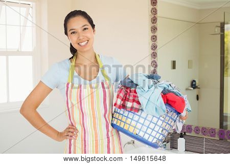 Happy woman with laundry basket against bathroom