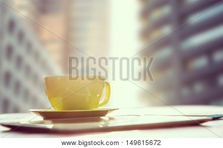 Cup of coffee and tablet pc against view of the city buildings