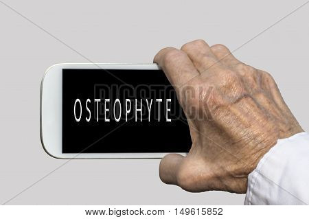 Smart phone in old hand with OSTEOPHYTE text on screen. Selective focus
