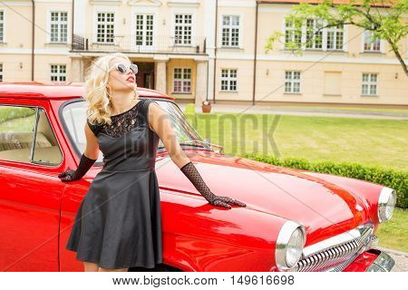 Woman standing next to red retro car